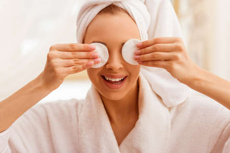 petite girl: Portrait of beautiful young woman in a bathrobe with a towel on her head covering her eyes with sponges and smiling.
