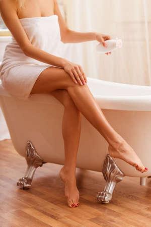 femmes nues sexy: Belle jeune femme dans une serviette tenant une bouteille de crème et de l'appliquer sur sa jambe alors qu'il était assis sur le bain, recadrée