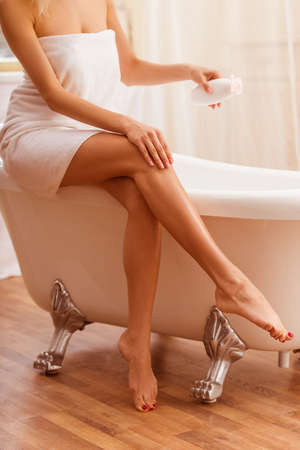 mujeres jovenes desnudas: Joven y bella mujer en una toalla con una botella de crema y aplicarlo en su pierna mientras está sentado en el baño, se ha cosechado