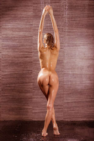 nude babe: Back view of passionate beautiful young naked woman taking shower, stretching up her hands