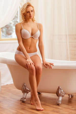 sexy nude women: Beautiful young woman in white underwear looking away and posing, sitting on a bath in the bathroom.