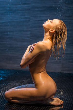 erotic breast: Side view of passionate beautiful young naked woman enjoying pleasant shower, sitting on her knees with closed eyes and covering her breast Stock Photo