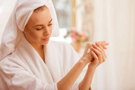 petite girl: Beautiful young woman in a bathrobe with a towel on her head applying cream on her hands, standing in the bathroom Stock Photo
