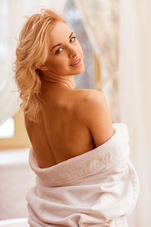 erotic girl: Portrait of beautiful young woman in a bathrobe looking at camera and posing, standing turned with bare shoulders Stock Photo