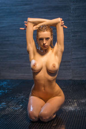 nude blond: Passionate beautiful young naked woman enjoying pleasant shower, sitting on her knees, keeping hands up and looking at camera