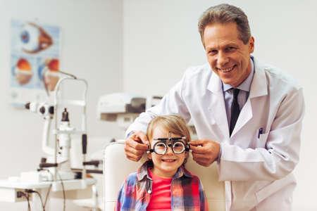 hombres guapos: Apuesto oftalm�logo de mediana edad examinar ni�o peque�o con equipos modernos, ambos sonriendo Foto de archivo