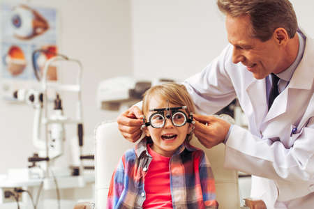 Handsome middle aged ophthalmologist examining little boy with modern equipment, both smiling Banque d'images