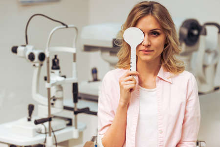 one eye: Young beautiful woman at the ophthalmologist on consultation, covering one eye and checking her visual acuity