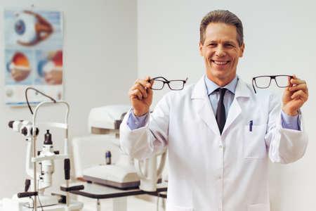 Knappe midden oude oftalmoloog die oogglazen houdt en glimlacht terwijl status in zijn bureau