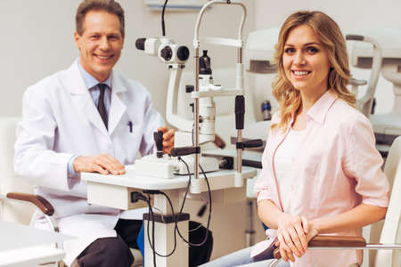 diopter: Handsome ophthalmologist examining beautiful woman with modern equipment, both looking at camera and smiling