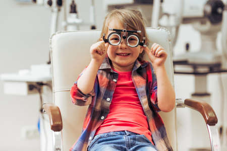 correcting: Little boy looking at camera and smiling while sitting on chair at the ophthalmologist