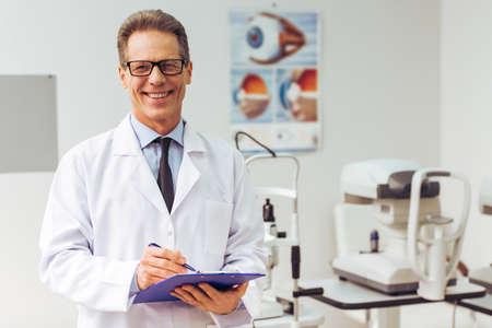 그의 사무실에서 서있는 동안 메모를 만들고 웃 고 잘 생긴 중간 나이 든된 안과 의사
