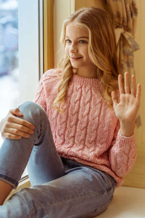 schoolgirl: Lovely teenage girl waving and smiling while sitting on the window sill in the room