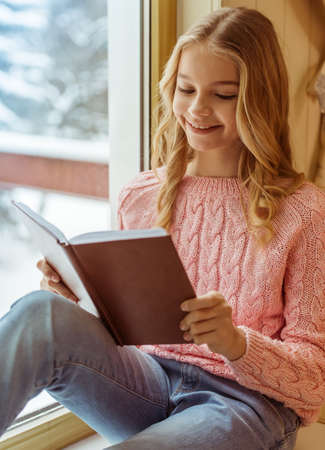 sill: Lovely teenage girl reading a book and smiling while sitting on the window sill