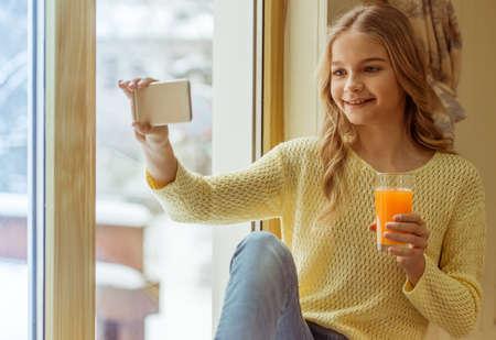 colegiala: Adolescente encantador con un vaso de zumo, que hace una foto y sonriendo mientras est� sentado en el alf�izar de la ventana