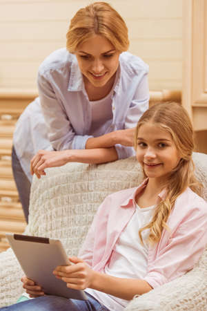 the schoolgirl: Lovely teenage girl using a tablet, looking at camera and smiling while sitting on the armchair, mother leaning on the armchair