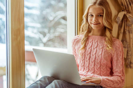 the schoolgirl: Lovely teenage girl using a laptop, looking at camera and smiling while sitting on the window sill in the room