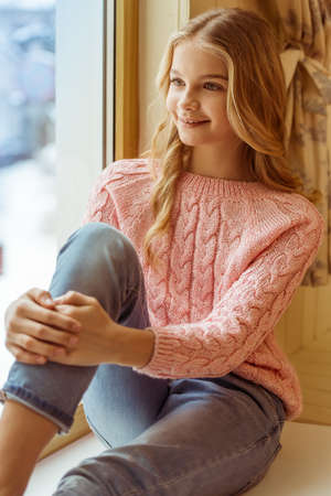 pullover: Lovely teenage girl smiling while sitting on the window sill in the room Stock Photo