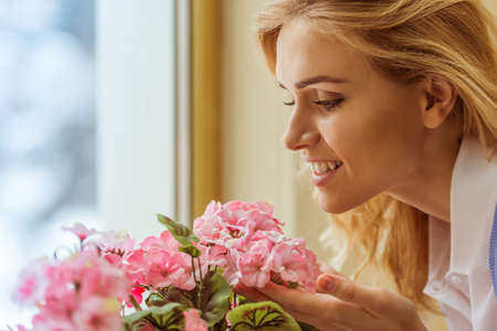 scent: Side view of a beautiful young woman enjoying the scent of flowers, close-up Stock Photo
