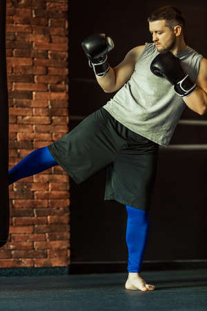 bout: Young kickboxer in boxing gloves practising with punching bag in a fight club Stock Photo