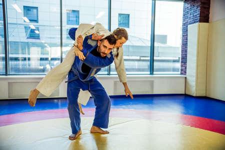 judo: Dos luchadores de judo que muestran la habilidad técnica, mientras que la práctica de artes marciales en un club de la lucha