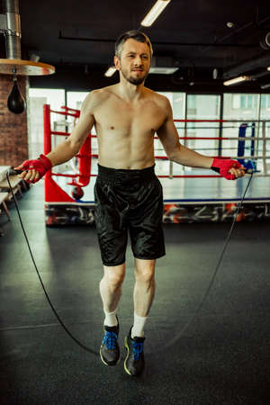 Middle aged boxer warming up with jumping rope in a fight club Stock Photo