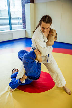 bout: Two judo fighters showing technical skill while practicing Martial arts in a fight club