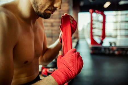 bout: Boxer wrapping his hands, ready to fight, close-up