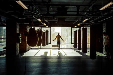 Men warming up in modern fight club with punching bags of different shapes for practicing martial arts Stock Photo