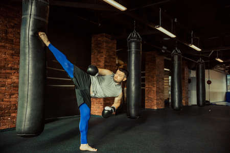 kickboxer: Young kickboxer in boxing gloves practising with punching bag in a fight club Stock Photo