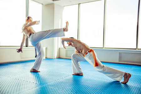 bout: Two capoeira performers showing technical skill while dancing in a fight club Stock Photo