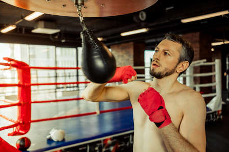 bout: Middle aged boxer practising with little punching bag while warming up in a fight club