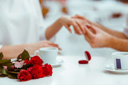 proposal of marriage: Handsome man putting wedding ring on and proposing to his beautiful woman in cafe. Bunch of red roses on a table, close-up