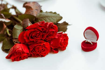 El manojo de rosas rojas, anillos de boda y del amor - todo lo que necesita para la propuesta de matrimonio! Sobre un fondo blanco