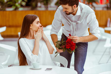 proposal: Handsome man with bunch of red roses and wedding ring proposing to his beautiful woman in cafe Stock Photo