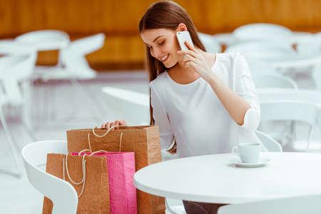 Schöne junge Frau in der weißen Bluse auf einem Handy sprechen und Kaffee trinken, während im Café ruhen nach dem Einkaufen zu tun