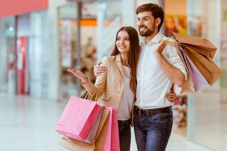 centro comercial: Feliz pareja joven y bella con sus bolsas de compras, mirando al escaparate y sonriendo mientras está de pie en el centro comercial