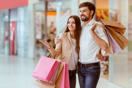 caucasian: Happy beautiful young couple holding shopping bags, looking upon showcase and smiling while standing in mall Stock Photo