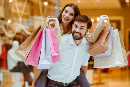 sales lady: Happy beautiful young couple holding shopping bags while standing in mall. Woman pickaback