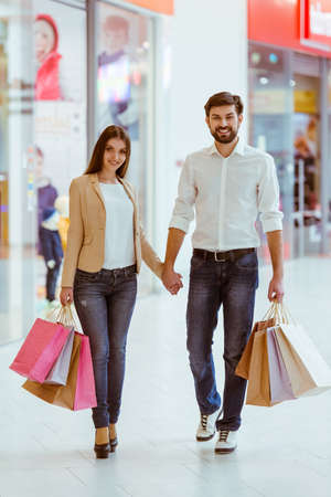 Happy beautiful young couple holding shopping bags, holding hands and smiling while doing shopping in mall Stock Photo