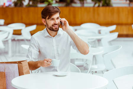 white shirt: Handsome young man in white shirt talking on a mobile phone, drinking coffee and smiling while resting in cafe after doing shopping Stock Photo