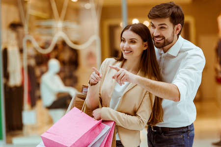 shopping centre: Happy beautiful young couple holding shopping bags, looking upon showcase and pointing while standing in mall Stock Photo