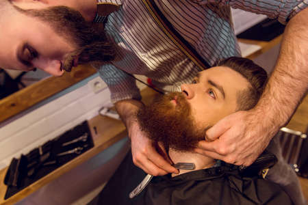 muscled: Attractive muscled bearded barber shaving handsome young customer at the barber shop