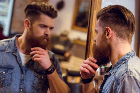 Apuesto joven barbero barba mirando en el espejo y el ajuste de la barba mientras está de pie en la peluquería Foto de archivo