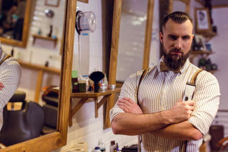 handsome men: Attractive muscled bearded barber holding a hair trimmer and looking at camera while standing in the barber shop Stock Photo