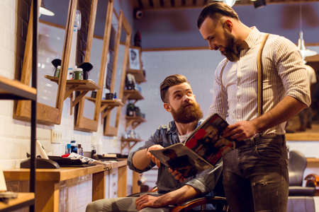 muscled: Attractive muscled bearded barber and handsome young customer reading a magazine and choosing haircut at the barber shop