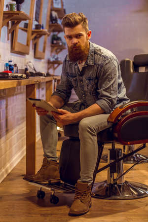 barber chair: Handsome young bearded man using a tablet and looking at camera while sitting on a chair at the barber shop Stock Photo