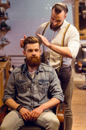 muscled: Attractive muscled bearded barber styling handsome young bearded customer hair at the barber shop Stock Photo