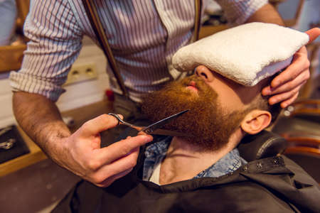 muscled: Attractive muscled bearded barber cutting handsome young customer beard at the barber shop
