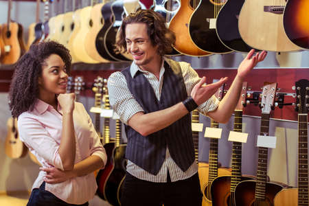afro man: Beautiful Afro-American girl and handsome man choosing a guitar and smiling while standing in a musical shop Stock Photo